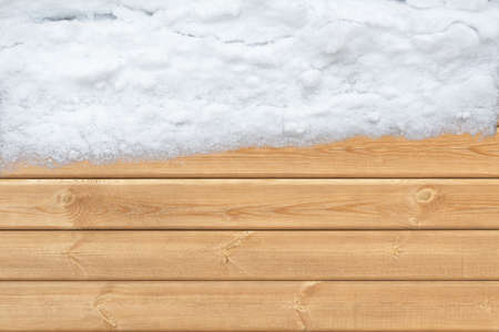 phon: Top view of wooden surface with snow on one side