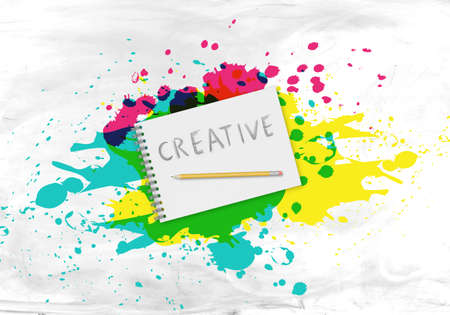 writing pad: A writing pad with the word creative and a pencil in the center of splatters  on a white and grey background Stock Photo
