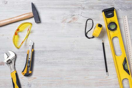 herramientas de trabajo: Vista superior de instrumentos y herramientas de construcción en el banco de trabajo de bricolaje de madera con espacio abierto en el centro.