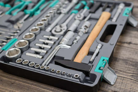 An open black toolbox with different instruments on wooden surface