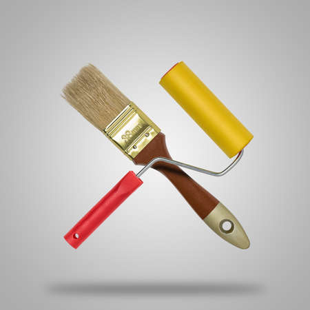 construction industry: Brush and roller paint in gray background like icon Stock Photo