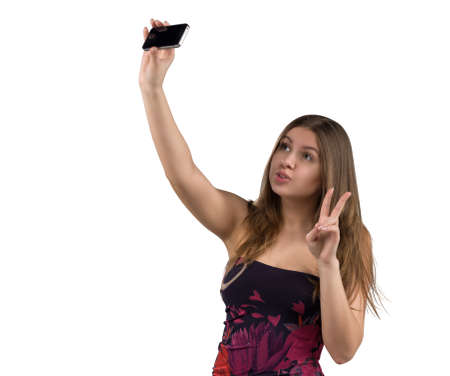 Portrait of attractive and hot girl in short tight dresses making selfie on smartphone, isolated on white background. Stock Photo