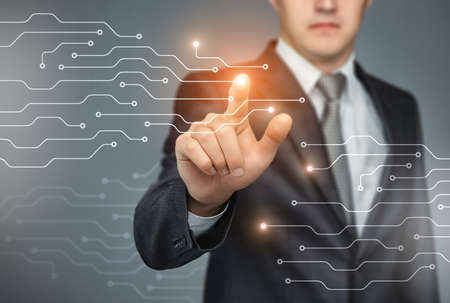 Business man touch digital icons and charts on a the holographic interface. Virtual technology concept Stock Photo
