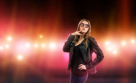 celebrities: Sexy young woman in leather jacket and sunglasses is surrounded by care and camera flash. Celebrity, model, star. Stock Photo