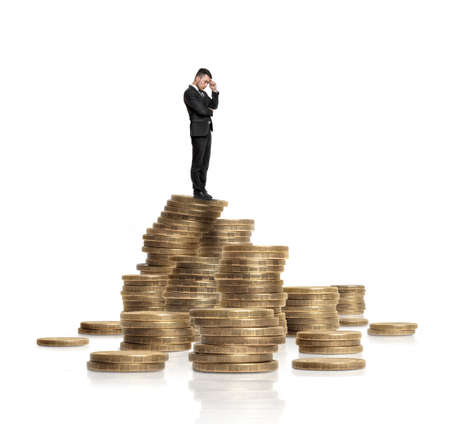 budgetary: A businessman in a black suit touches his forehead with his hand standing on a heap of glittering golden coins isolated on a white background