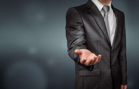 Businessman standing sideways in a gray suit stretches out his right hand on gray background