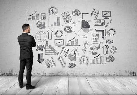 estadistica: Vista posterior de un hombre en un traje negro mirando a una pared blanca con fotos y diagramas gráficos dibujados a mano relacionados con la economía y la estadística