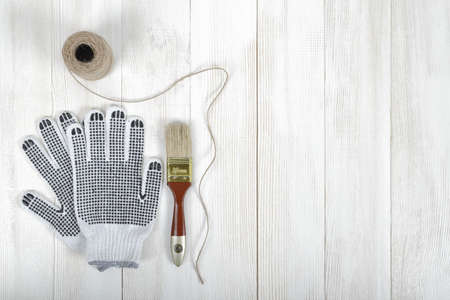 hank: An art composition featuring of gloves, brush and a twine lying on a white wooden surface. Tools.