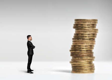 Ein Geschäftsmann stehen im Profil mit seinen Armen vor einem Stapel von Skala Rubel Münzen gefaltet.