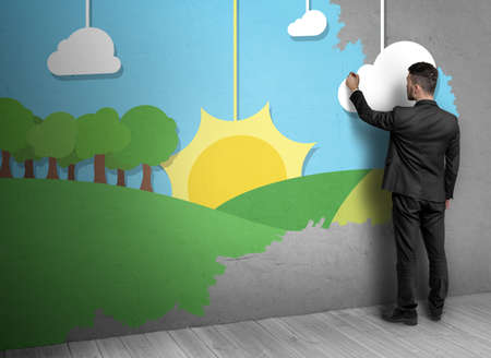 delineate: Back view of a man in a black suit drawing nature with cloudy blue sky and  the rising sun over the field on a concrete wall. Stock Photo