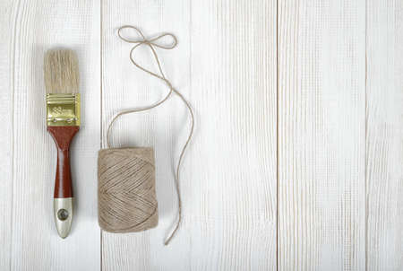 handtools: Twine and brush on wooden DIY workbench with open space right side. Top view of the composition. Stock Photo