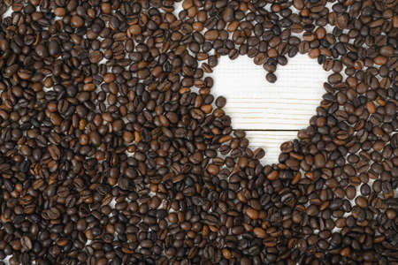 scattered in heart shaped: Top view of coffee beans in heart shape on wooden surface. Concept of love with coffee.