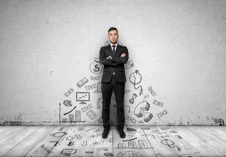 looking directly at camera: Businessman standing with folded arms looking directly at the camera on concrete wall with business sketches on it passing to the floor. Front view.