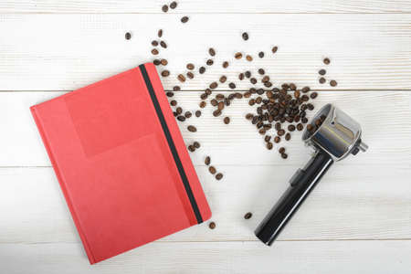 bottomless: Coffee stuff with a portafilter of a home espresso machine, red folder and scattered coffee beans on wooden surface in top view