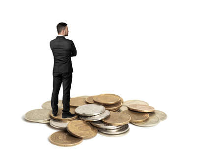 budgetary: Back view of cutout businessman in a black suit with folded arms standing on a copper heap of ruble coins