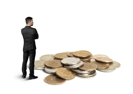 Back view of cutout businessman in a black suit with folded arms standing in front of  a copper heap of ruble coins