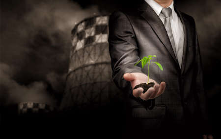 thermal power plant: Sprout growing on the ground in hand of businessman standing over thermal power plant background. Concept. Stock Photo