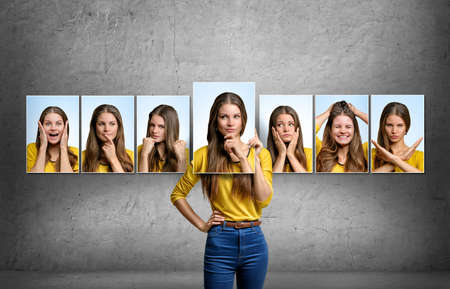 Young beautiful girl holds and changes her face portraits with different emotions. Reklamní fotografie - 55737031
