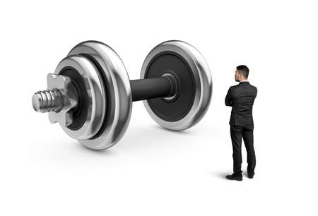 crossed arms: Cutout businessman with crossed arms standing in front of increased dumbbell looks at it. Stock Photo