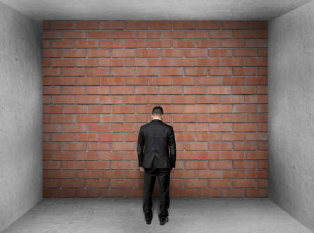 unavailability: A businessman with bowed head stands in front of a brick wall in interior. Stock Photo