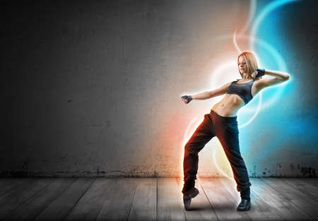 gorgeous girl: Girl dancer stands leaning back with lifted up left hand bent at the elbow. Glowing light lines are following her move on dark background. Stock Photo