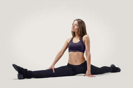 pleasing: Pleasing young fitness woman in sportswear sits on a splits looking up