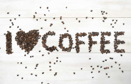 scattered in heart shaped: Top view of coffee beans spelled phrase I love coffee on light wooden surface. Stock Photo