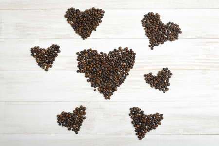 scattered in heart shaped: Lots of hearts from coffee beans on wooden surface in top view.