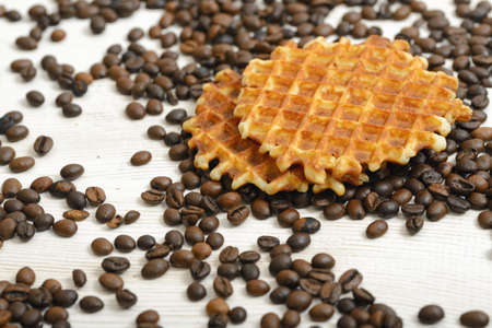belgian waffle: Belgian Waffle biscuit and coffee beans scattered on light surface.