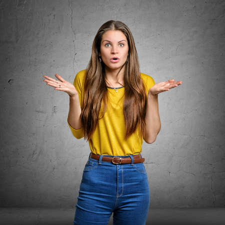 shrugs: Pretty woman shrugs shoulders with palms up and astonished expression on her face Stock Photo