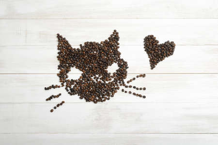 scattered in heart shaped: Heart and cat from coffee beans on wooden surface in top view.
