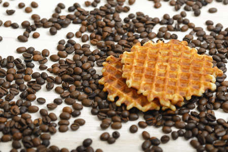waffle: Belgian Waffle biscuit and coffee beans scattered on light surface.