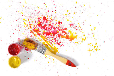 A paint brush with red and yellow gouache sprays near on white canvas in top view. Art composition. Stock Photo