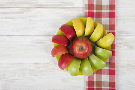 quartered: Yellow, green and red quartered apples laid out around the whole apple on a saucer. Table decoration.