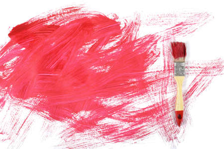 daub: Flat lay of paintbrush with red gouache daub on white canvas.