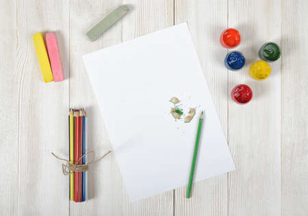 white chalks: Work place of designer with colored pencils, brush, gouache jars, colored chalks and a white paper in top view. Art disposition on wooden surface.