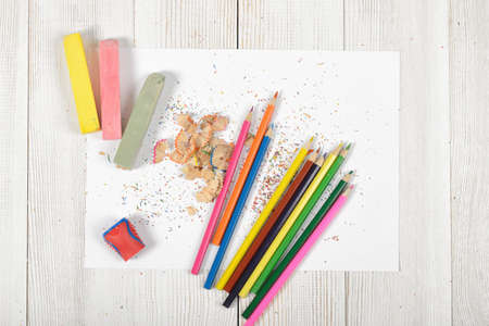 white chalks: Work stuff of designer lying on wooden surface in top view. Colored pencils, chalks, shavings, pencil sharpener and white paper. Stock Photo