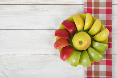 quartered: Yellow, green and red quartered apples laid out around the whole apple on a saucer. Stock Photo
