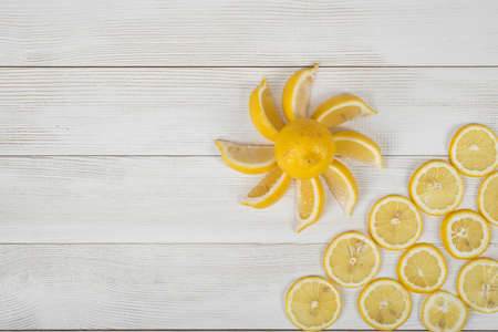 Lemon pieces laid out around the whole lemon into a revolving shape. Citrus slices are in a raw on the right corner in top view.