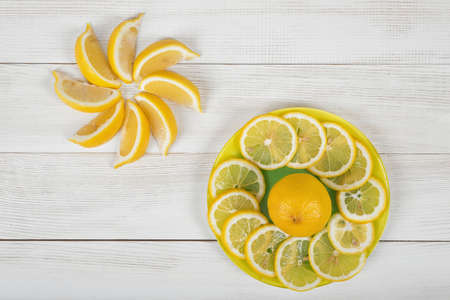 Citrus fruit slices arranged into a revolving shape. Lemon and orange are cut into slices and well decorated on a plate in top view. Stock Photo