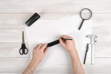 draftsman: Workplace of draftsman equipped with pencil, ruler, pen, stapler, scissors and magnifying glass. Hands of man holding centimeter ruler and draw on white paper. Top view.