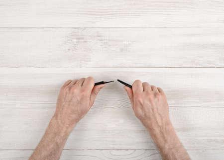 eraser mark: Masculine hands broke a black pencil. Nervous situation.