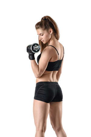 Back view of cutout young girl lifting a dumbbell for showing her power. Power training.