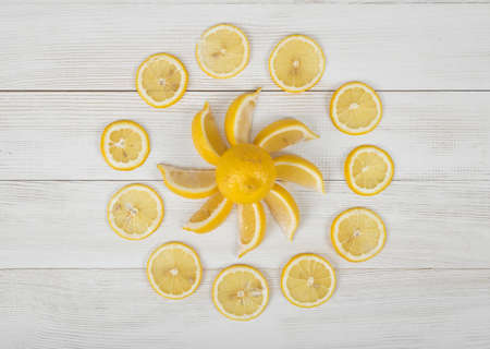 well laid: Flat lay of lemon pieces laid out into the sun shape and well decorated slices around it. Top view composition.