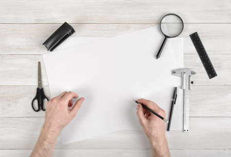 construction draftsman: Closeup hands of man holding pencil and draw on white paper in top view. Workplace of draftsman equipped with pencil, ruler, pen, stapler, scissors and magnifying glass.