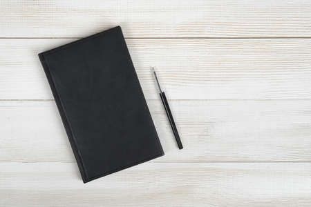 composition notebook: Flat lay of black notebook and black pen on light wooden surface. Composition. Stock Photo