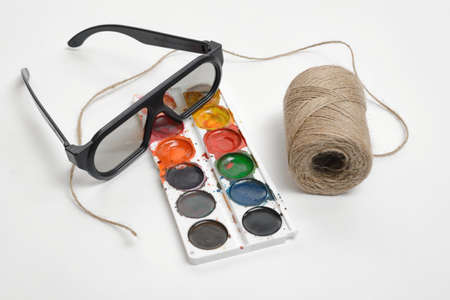 twine: Flat lay of art scene featuring of thread twine, glasses and watercolor paints isolated on a white background. Art design.