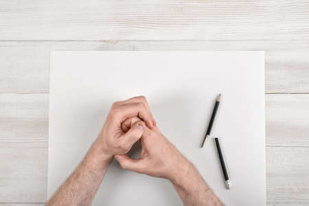 eraser mark: Closeup masculine folded hands on wooden panel with white paper and broken black pencil in top view. Worry process.
