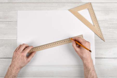 draftsman: Close-up of draftsman hands holding centimeter ruler and pencil. Measuring process. Work place of draftsman.