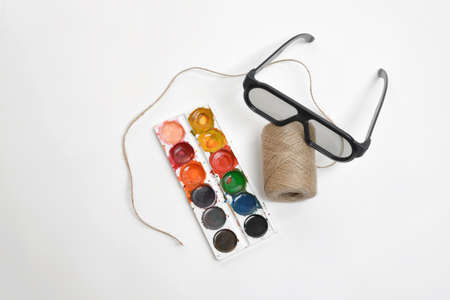 twine: Top view of art scene featuring of thread twine, glasses and watercolor paints on a white background. Equipment of art designer. Stock Photo